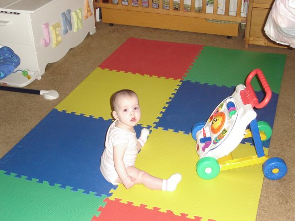 Jenna plays on a mat.